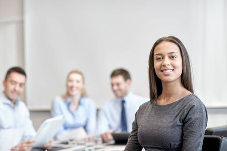 group meeting: business, people and teamwork concept - smiling businesswoman with group of businesspeople meeting in office