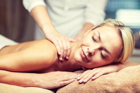 personas saludables: personas, belleza, spa, estilo de vida saludable y la relajación concepto - cerca de la hermosa mujer joven tendido con los ojos cerrados y con masaje de manos en el spa