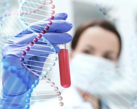 la ciencia, la química, la biología, la medicina y la gente concepto - cerca del científico de sexo femenino joven que sostiene el tubo de ensayo con la muestra de sangre en la investigación en laboratorio clínico sobre la estructura de la molécula de ADN