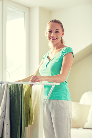 laundry concept: people, housework, laundry and housekeeping concept - happy woman hanging clothes on dryer at home