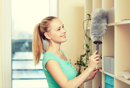 Domestic cleaning: people, housework and housekeeping concept - happy woman with duster cleaning at home Stock Photo