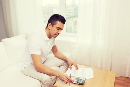 business savings: business, savings, finances and people concept - man with papers and calculator at home counting and filling tax form