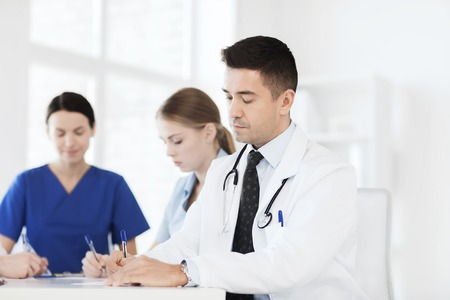 hospital notes: hospital, profession, people and medicine concept - group of happy doctors meeting and taking notes at medical office