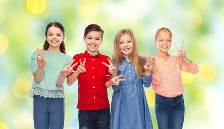 summer sign: childhood, fashion, friendship and people concept - happy smiling boy and girls showing peace hand sign over green summer holidays lights background