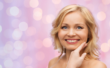 bare shoulders: beauty, people and skincare concept - smiling woman with bare shoulders touching face over pink lights background