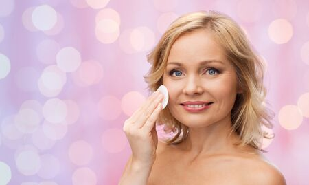 removing make up: beauty, people and skincare concept - young woman cleaning face and removing make up with cotton pad over pink lights background Stock Photo