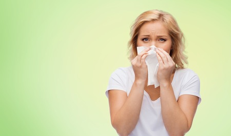 noses: people, healthcare, rhinitis, cold and allergy concept - unhappy woman with paper napkin blowing nose over green natural background
