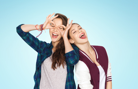 pretty young girl: people, friends, teens and friendship concept - happy smiling pretty teenage girls having fun and making faces over blue background Stock Photo