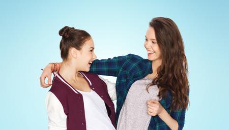 amigos abrazandose: personas, amigos, adolescentes y concepto de la amistad - Feliz sonriente Adolescentes bonitos que abrazan sobre el fondo azul Foto de archivo