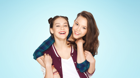 amigos abrazandose: people, friends, teens and friendship concept - happy smiling pretty teenage girls hugging over blue background