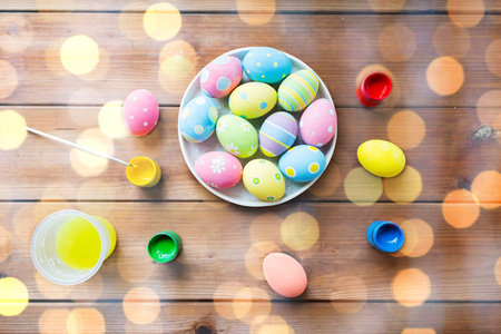 easter, holidays, tradition and object concept - close up of colored easter eggs on plate Stock Photo