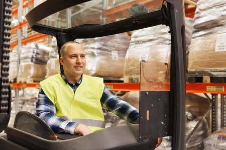 elevator operator: wholesale, logistic, loading, shipment and people concept - smiling man or loader operating forklift loader at warehouse Stock Photo