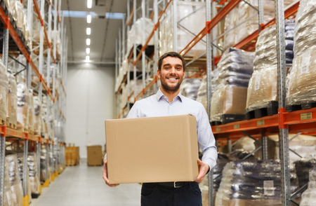 wholesale, logistic, business, export and people concept - happy man with cardboard parcel box at warehouse Stockfoto