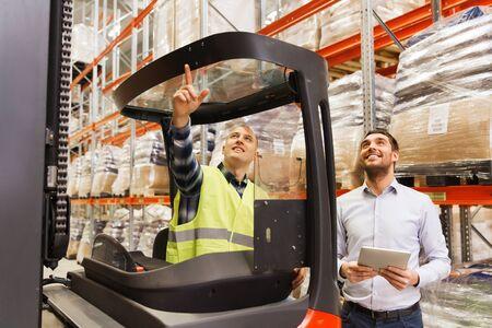 卸売、ロジスティック、読み込み中、出荷と人コンセプト - フォーク リフトと倉庫でタブレット pc コンピューターを持ったビジネスマンのローダー