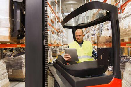 卸売、ロジスティック、読み込み中、出荷と人コンセプト - 人またはタブレット pc コンピューターとフォーク リフト ローダー ローダー倉庫でボッ