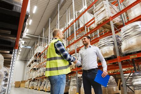卸売、物流、人々 およびエクスポート コンセプト - 肉体労働者やクリップボードの握手と倉庫で作る取り引きビジネスマン 写真素材 - 59195289