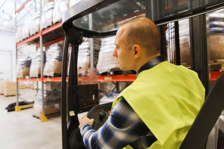 elevator operator: wholesale, logistic, loading, shipment and people concept - man or loader operating forklift loader at warehouse Stock Photo