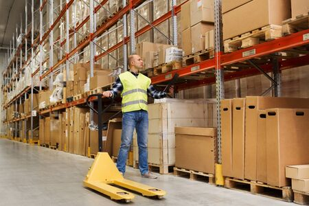 empty warehouse: wholesale, logistic, loading, shipment and people concept - man with empty loader and clipboard at warehouse