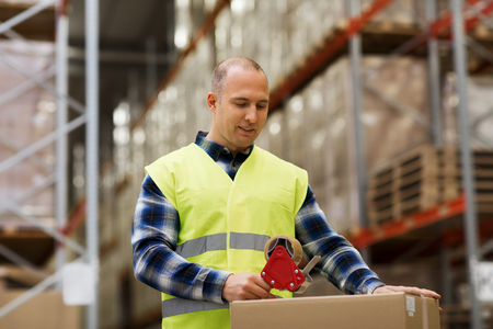 shipment package: logistic, delivery, shipment, people and export concept - happy man in safety vest packing box or parcel with scotch tape at warehouse or mail storage