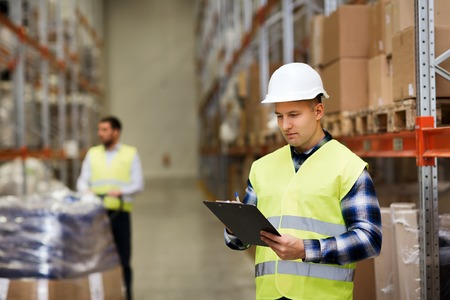 safety check: wholesale, logistic, people and export concept - man with clipboard in reflective safety vest at warehouse