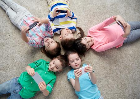 infanzia, la moda, l'amicizia e la gente il concetto - gruppo di felice sorridente bambini piccoli con gli smartphone si trova sul pavimento