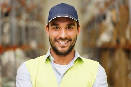 Großhandel, Logistik, Menschen und Export-Konzept - glücklicher Mann in der Schutzkappe und reflektierende Sicherheitsweste an Lager Standard-Bild
