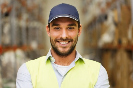 wholesale, logistic, people and export concept - happy man in cap and reflective safety vest at warehouse Stock Photo