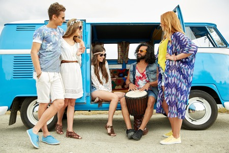 trip over: summer holidays, road trip, vacation, travel and people concept - happy young hippie friends with tom-tom drum playing music over minivan car Stock Photo