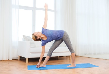 woman posture: fitness, sport, people and healthy lifestyle concept - woman making yoga triangle pose on mat