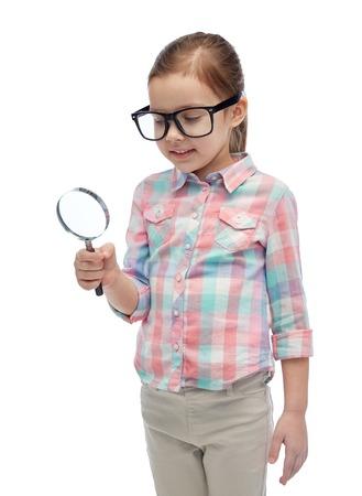 descubridor: la infancia, la educación, la investigación, el descubrimiento y el concepto de la gente - niña feliz en gafas con la lupa Foto de archivo