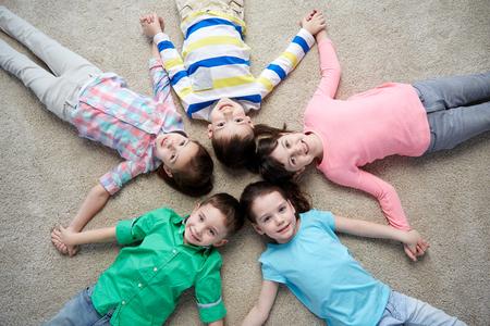 niños sonriendo: la infancia, la moda, la amistad y el concepto de personas - grupo de felices los niños pequeños sonriente acostado en el piso y de la mano Foto de archivo
