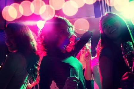 ragazze che ballano: partito, feste, celebrazioni, vita notturna e la gente concept - sorridente amici con bicchieri di champagne in centro Archivio Fotografico