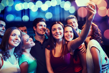 teen: party, technology, nightlife and people concept - smiling friends with smartphone taking selfie in club