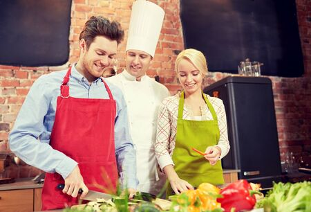 kulinarne: cooking class, culinary, food and people concept - happy couple and male chef cook cooking in kitchen