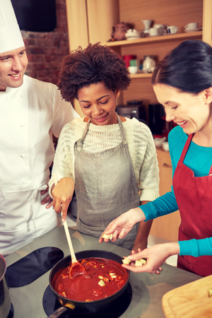 souse: cooking class, culinary, food and people concept - happy group of women and male chef cook cooking tomato souse in kitchen