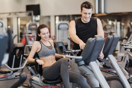 stationary: sport, fitness, lifestyle, technology and people concept - happy woman with trainer working out on exercise bike in gym Stock Photo