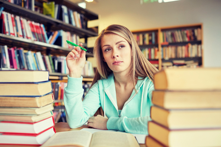 bored student: people, knowledge, education, literature and school concept - bored student girl or young woman with books dreaming in library