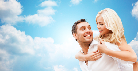 romance sky: romance, people, love and dating concept - happy couple over blue sky and clouds background