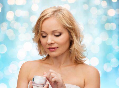 productos de belleza: belleza, gente, cuidado de la piel y cosméticos concepto - mujer de mediana edad con el tarro de crema sobre las vacaciones azules fondo de las luces