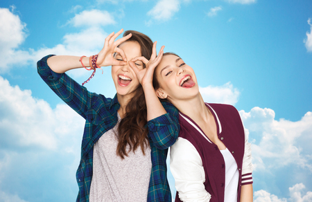 smiling faces: people, friends, teens and friendship concept - happy smiling pretty teenage girls having fun and making faces over blue sky and clouds background Stock Photo