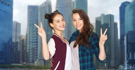 amigos abrazandose: people, teens, friendship, travel and tourism concept - happy smiling pretty teenage girls hugging and showing peace hand sign over singapore city background Foto de archivo