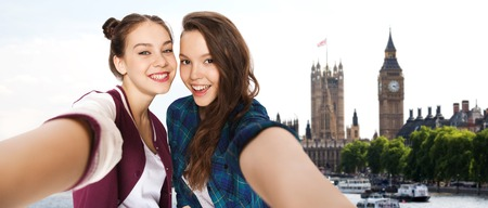 britain: people, travel, tourism and friendship concept - happy smiling pretty teenage girls taking selfie over london background