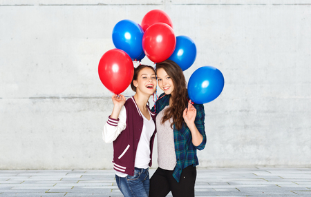 helium: people, friends, teens, holidays and party concept - happy smiling pretty teenage girls with helium balloons over gray stone wall background