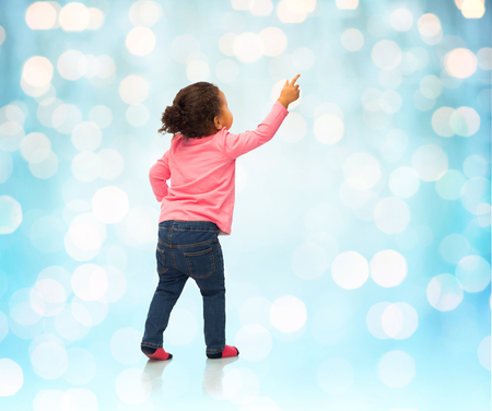 decent: people, race, ethnicity and childhood concept - happy african american baby girl pointing finger to something from back over blue holidays lights background Stock Photo