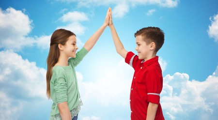 clouds making: childhood, friendship, gesture and people concept - happy smiling boy and girl making high five over blue sky and clouds background