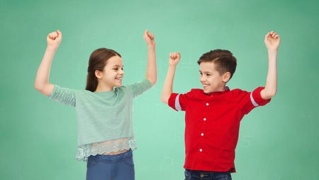school boy: friendship, education, school, gesture and people concept - happy smiling boy and girl raising fists and celebrating victory over green chalk board background