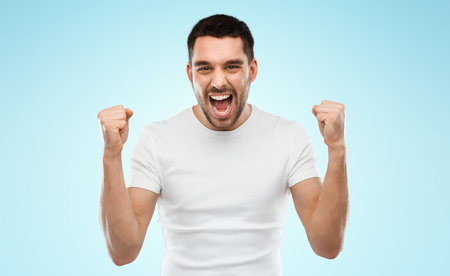 background person: emotion, success, gesture and people concept - young man celebrating victory over blue background Stock Photo