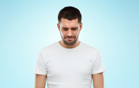 white man: emotion, sadness and people concept - unhappy young man over blue background