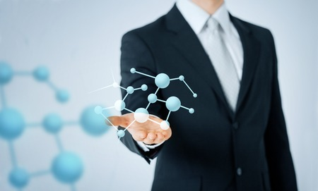 people, business, chemistry, science and biology concept - close up of man hand showing molecule formula projection Stock Photo