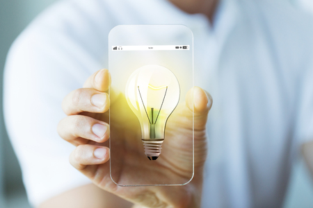 close icon: business, technology, startup, idea and people concept - close up of male hand holding and showing transparent smartphone with light bulb icon Stock Photo